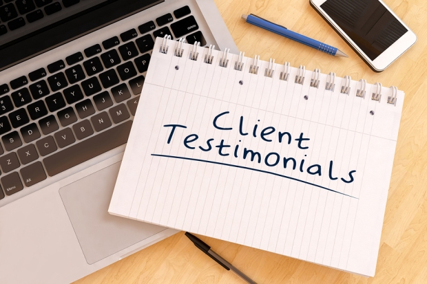 Client Testimonials handwritten text in a notebook on a desk with a laptop and pencils